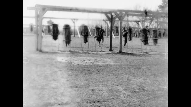 long shot us soldiers run to hanging dummies and stab them with bayonets then move on as another group follows as they train for service in wwi at... - 1910 stock videos and b-roll footage