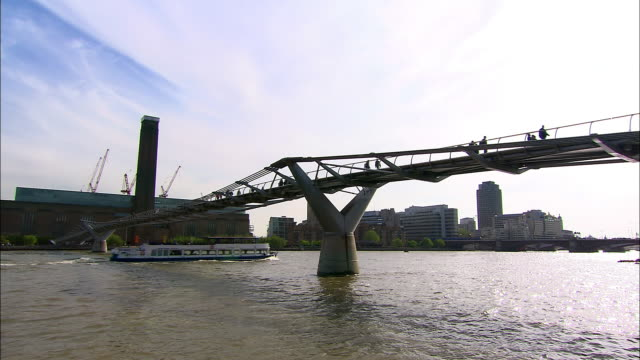 long shot view across river thames of millennium bridge and tate modern / london - はしけ点の映像素材/bロール