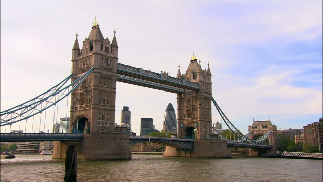 long shot view across river thames of natwest tower and gherkin framed by tower bridge / london - 跳開橋点の映像素材/bロール