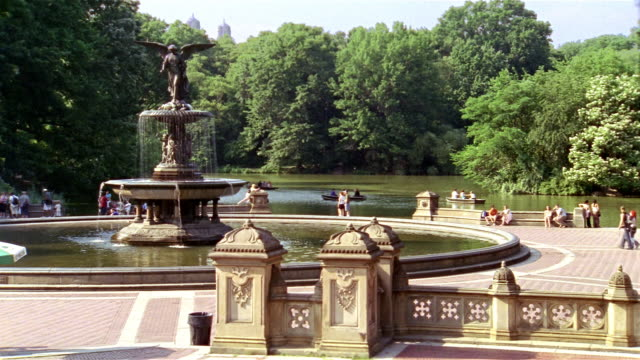 vídeos de stock e filmes b-roll de long shot view of bethesda fountain and the lake in central park/ visitors walking on terrace/ new york city - fonte bethesda