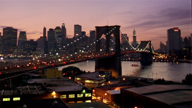 long shot view of brooklyn bridge over east river and manhattan skyline at sunset / new york city - brooklyn bridge stock videos & royalty-free footage