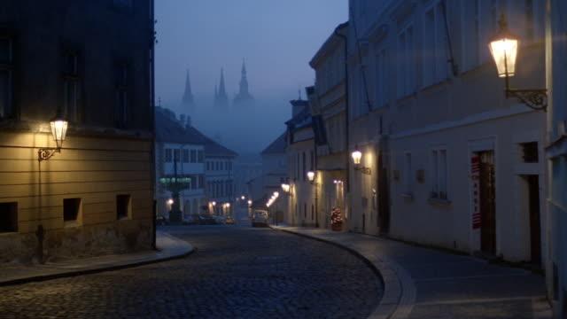 long shot view of curving street on foggy day at twilight / prague - praga video stock e b–roll