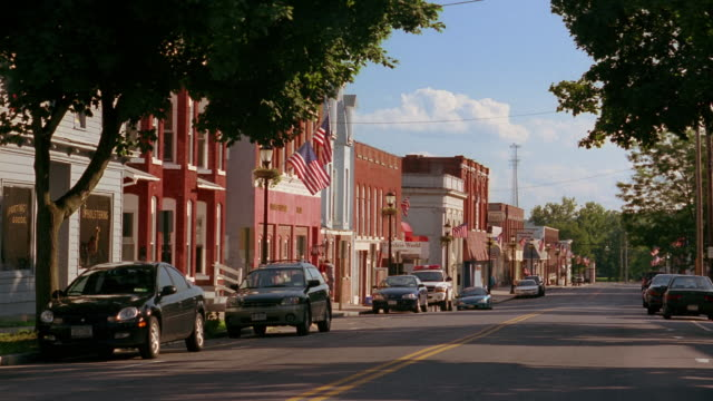 long shot view of light traffic on main street in small town - small town stock videos & royalty-free footage