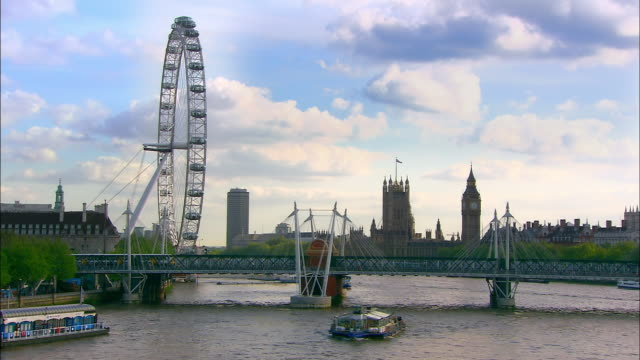 long shot view of london eye, palace of westminster and train crossing hungerford bridge over thames / london - lastkahn stock-videos und b-roll-filmmaterial