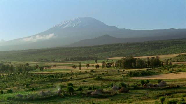 long shot view of mt. kilimanjaro and masai village / tanzania - mt kilimanjaro stock videos & royalty-free footage
