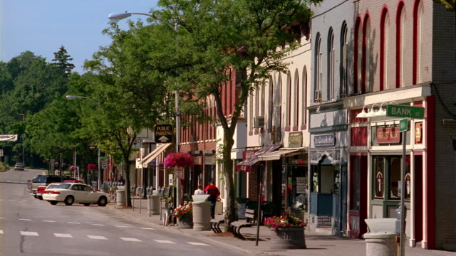 long shot view of shops and pedestrians on main street in a small town - small town stock videos & royalty-free footage