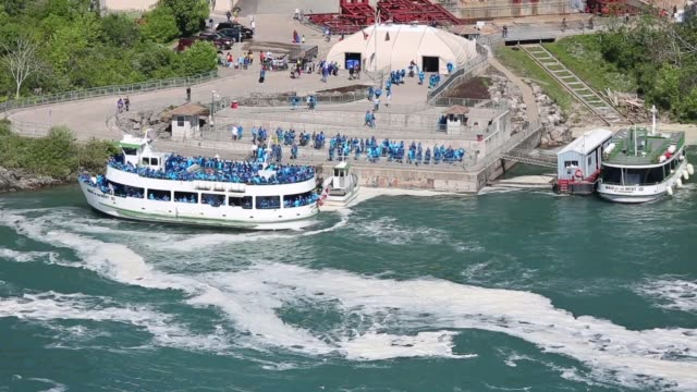 Long shot Views of Niagara Falls from the US side and the Maid of the Mist tourist boat approaching the falls with rainbows in the mist Border Patrol...