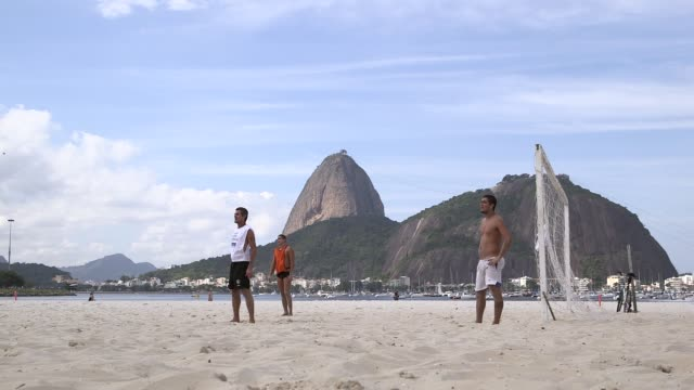 vídeos de stock, filmes e b-roll de long shot white shirts goalkeeper makes a save amateur teams play play football on botafogo beach rio de janeiro brazil on june 9 2013 - baía de guanabara