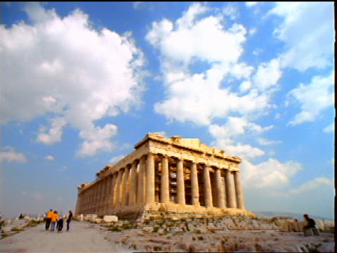 long shot wide shot tilt down tourists walking by Parthenon under blue sky / Acropolis / Athens, Greece