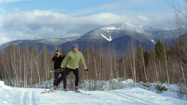 Long shot woman and man cross-country skiing