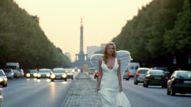 Long shot woman dressed as angel walking down middle of street with Siegessaule in background / Berlin, Germany