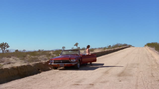 long shot woman getting out of convertible and opening hood / looking up and down desert road - bonnet stock videos & royalty-free footage