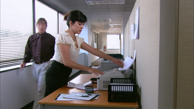 long shot woman using fax machine / getting frustrated at broken machine as co-workers walks by without offering help - place of work stock videos & royalty-free footage