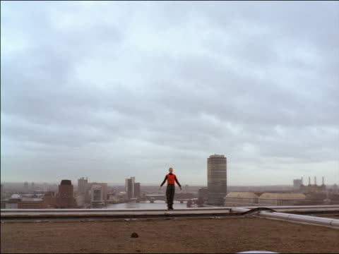 long shot woman with shaved head in red vest standing on edge of roof spreading her arms / city skyline in background