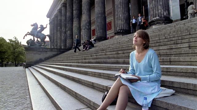 vídeos y material grabado en eventos de stock de long shot woman writing in diary while sitting on steps of altes museum (old museum) / berlin - botella de agua