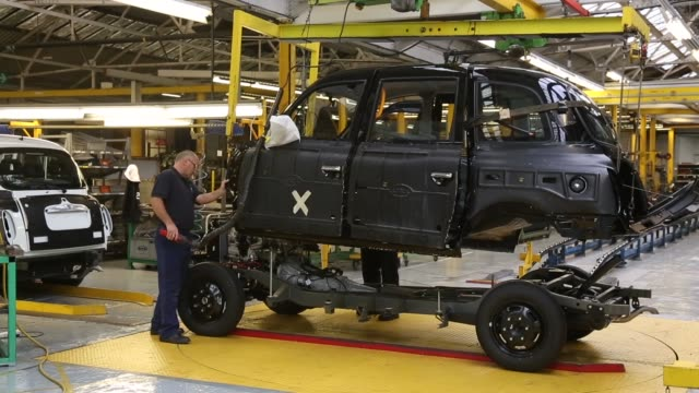 long shot workers inside the factory of the london taxi company attach the body of a tx4 london taxi to its chassis on september 11 2013 in coventry... - fahrgestell stock-videos und b-roll-filmmaterial