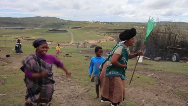long shot, xhosa women sing and dance as young men take part in a manhood ceremony in qunu ahead of the funeral of nelson mandela on december 13,... - mascolinità video stock e b–roll