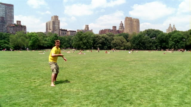 long shot young man throwing frisbee at cam / central park / new york city - sheep meadow central park stock videos and b-roll footage