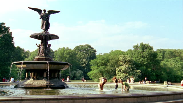 long shot young men and woman playing around in bethesda fountain / central park / new york city - fountain stock videos & royalty-free footage