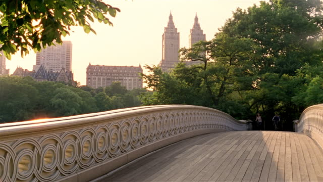 Long shot young woman and man riding bikes across Bow Bridge in Central Park / New York City