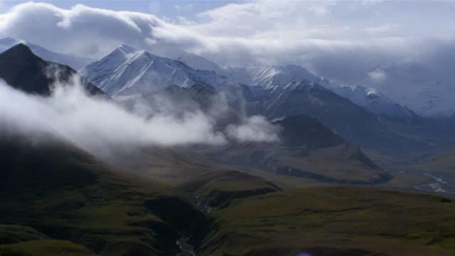 long shot zoom in fog rolling over mountains and toklat river valley / denali national park / alaska - denali national park stock videos & royalty-free footage