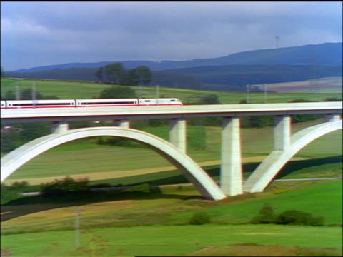 vídeos de stock, filmes e b-roll de long shot zoom in pan high speed commuter train going over bridge through bavarian countryside / germany - trem de passageiros trem