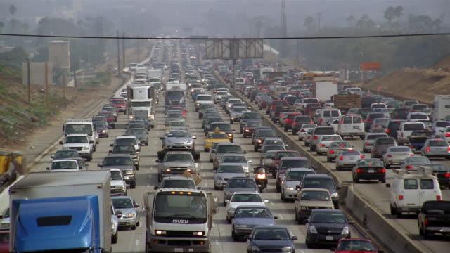 Long shot zoom in lanes of heavy traffic on highway / Los Angeles, California