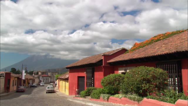 long shot zoom out cars parked on winding street in small village with colored houses on either side / man walking down street / fluffy clouds in sky / antigua, guatemala - guatemala stock videos & royalty-free footage