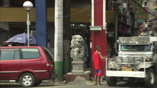 long shot zoom out - statue of a chinese guardian lion (aka foo dog) to busy street with jeepney taxis in chinatown / manilla philippines - animal representation stock videos and b-roll footage