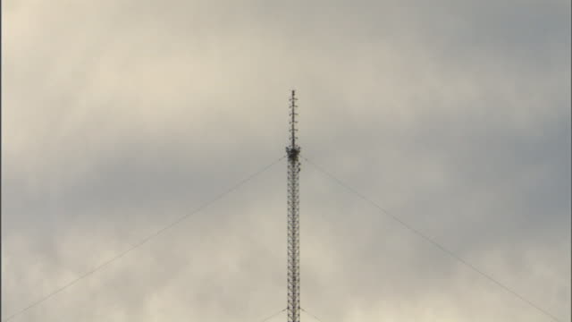 long shot zoom-in - a construction worker works in the center of a tall communication tower. / north carolina, usa - communications tower stock videos & royalty-free footage