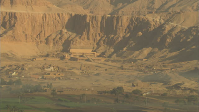 long shot, zoom-out - ancient egyptian ruins overlook the verdant farmlands of the nile river valley - tal der könige stock-videos und b-roll-filmmaterial