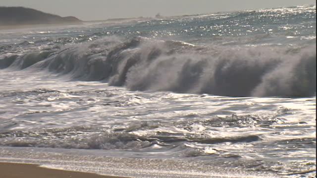 stockvideo's en b-roll-footage met long shot zoom-out - storm waves wash onto a sandy beach. / sri lanka - zeegezicht