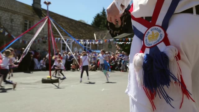 stockvideo's en b-roll-footage met long shots of maypole dancing. villagers celebrate traditional may bank holiday fayre on may 06, 2013 in glastonbury, england - festivalganger