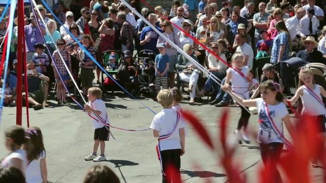 vídeos de stock, filmes e b-roll de long shots of maypole dancing villagers celebrate traditional may bank holiday fayre on may 06 2013 in glastonbury england - 1 de maio