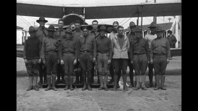 vidéos et rushes de long side shot of aviators standing in formation at training school / group of aviators stands in front of plane / aviators crowd around plane and... - biplan