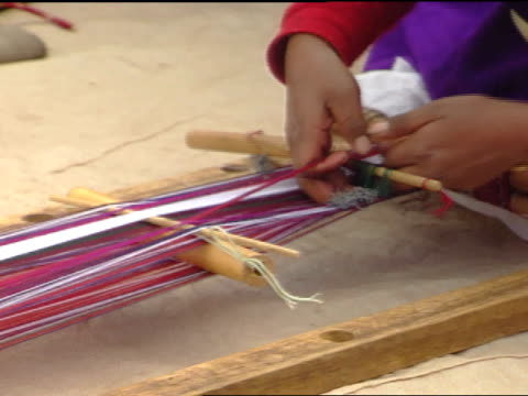long strands of colored threads, female hands working on hand-made loom, weaving thread, tightening material, hand-woven textiles. - weaving stock videos & royalty-free footage