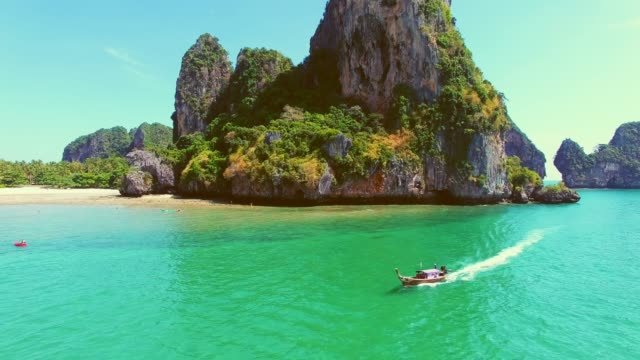 vídeos de stock e filmes b-roll de long tail boat passing through tropical islands - ilhas phi phi