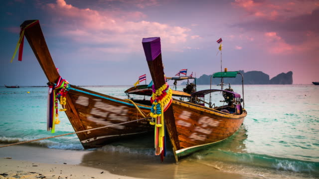 vídeos de stock e filmes b-roll de long tail boats on tropical beach in thailand - ilhas phi phi