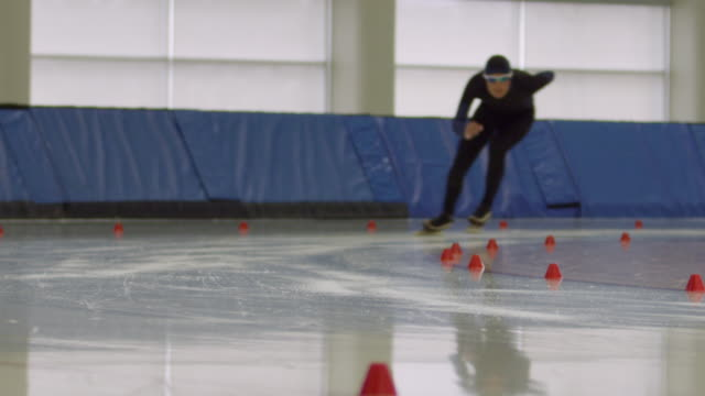 MS SLO MO Long track speed skater coming around corner on track in arena