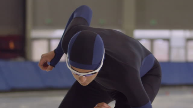 cu slo mo long track speed skater in starting position before race on ice in arena - 集中点の映像素材/bロール