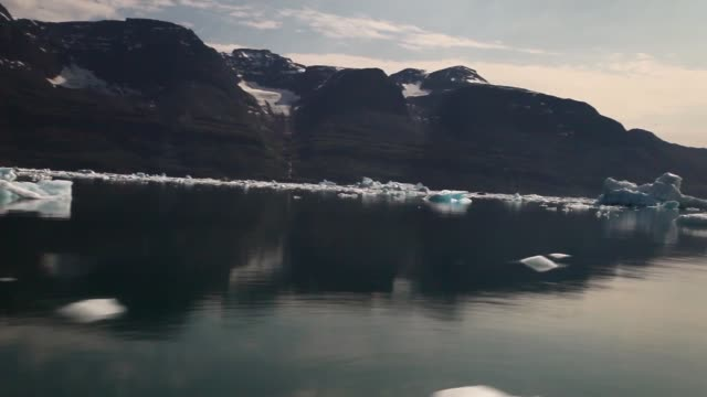 Long Tracking Shot Calved icebergs from the nearby Twin Glaciers are seen floating on the water on July 30 2013 in Qaqortoq Greenland Boats are a...
