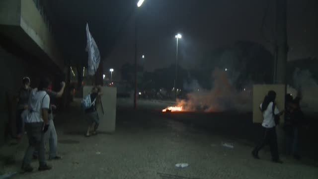 Long Tracking Shot Fires in streets protesters throwing stones and police firing teargas and rubber bullets