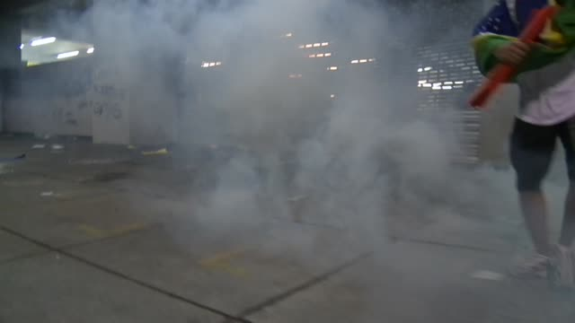 vídeos de stock, filmes e b-roll de long tracking shot fires in streets protesters throwing stones and police firing teargas and rubber bullets - carro blindado