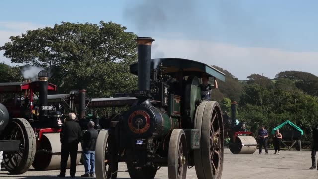 long tracking shot of a approaching steam engine exhibitors prepare their steam engines to show at the cornish steam and country fair at the... - traktor stock-videos und b-roll-filmmaterial