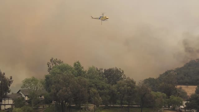 long tracking shot of a fire helicopter dropping water on the fire a ventura county fire fighting helicopter makes a water drop to battle an out of... - camarillo stock videos & royalty-free footage