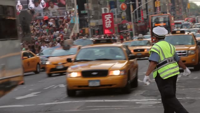 long tracking shot of a policewoman directing traffic at times square new york - police woman stock videos & royalty-free footage
