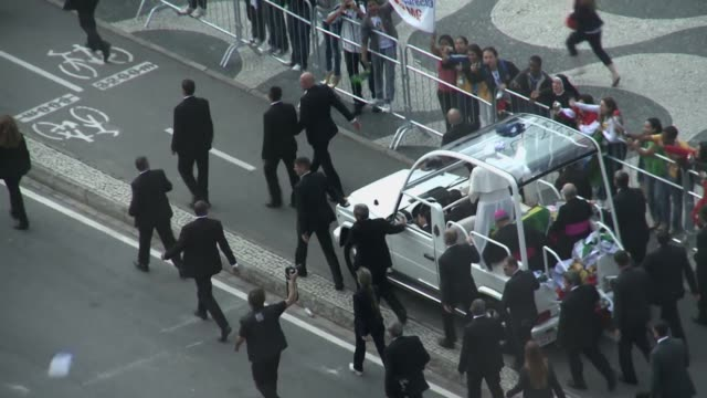 long tracking shot, the pope is making his way to copacabana beach in the popemobile greeted by thousands of euphoric believers. pope francis arrived... - ローマ法王専用車点の映像素材/bロール