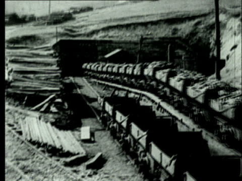 vídeos de stock e filmes b-roll de 1927 b/w ws long train of coal mine carts laden with bituminous coal emerging from underground coal mine/ pennsylvania, usa - mina de carvão