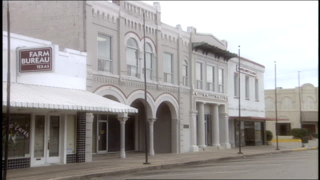 long view of small town main st in bryan texas - 道路名の標識点の映像素材/bロール