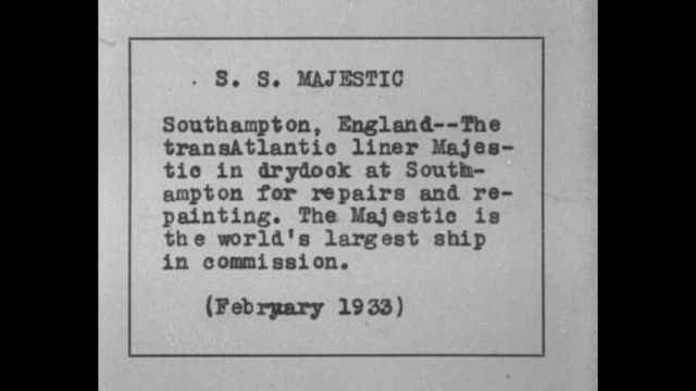 Long view of SS Majestic at dock / CU of side of ship with the word MAJESTIC written on its side deckhands scurry dockside to pull up anchor /...